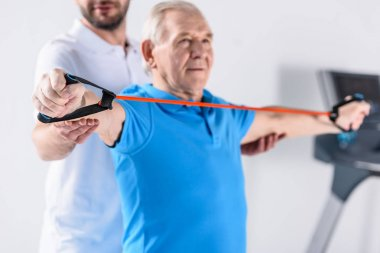 partial view of rehabilitation therapist assisting senior man exercising with rubber tape
