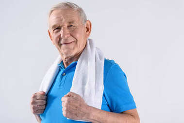 portrait of smiling senior man with towel looking at camera isolated on grey