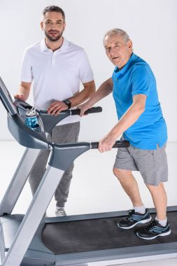 rehabilitation therapist and senior man on treadmill isolated on grey