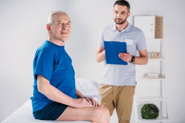 selective focus of rehabilitation therapist with notepad and senior man on massage table