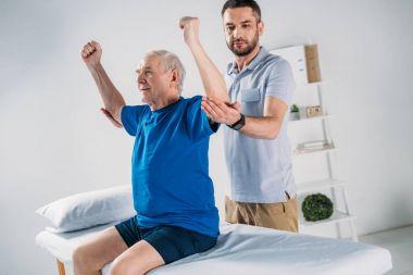 portrait of focused physiotherapist doing massage to senior man on massage table
