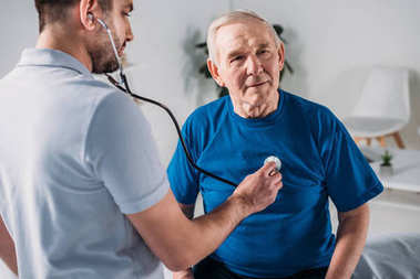 rehabilitation therapist with stethoscope checking senior mans heartbeat