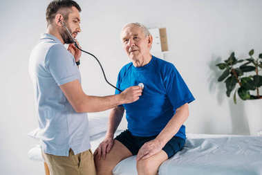 rehabilitation therapist with stethoscope checking senior mans heartbeat