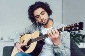 Fotografia serio bello chitarrista a suonare la chitarra acustica a casa