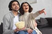 Fotografie směje se mladý pár držící misku popcornu a sledování komedie doma