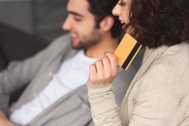 girlfriend holding credit card and looking away at home