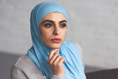 portrait of pensive beautiful muslim woman in hijab looking away at home