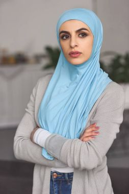 beautiful serious muslim woman in hijab standing with crossed arms and looking away at home