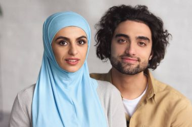 portrait of muslim couple looking at camera at home