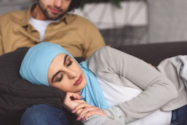 muslim girlfriend in hijab sleeping on boyfriends legs at home