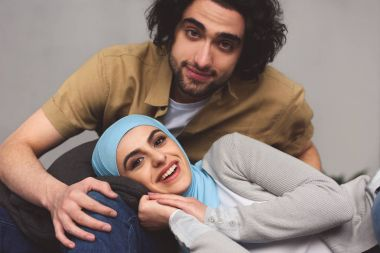 smiling muslim couple looking at camera at home