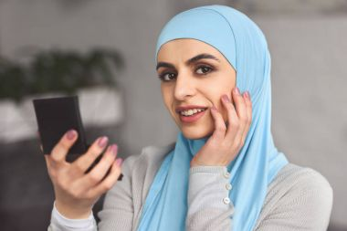 smiling beautiful muslim woman in hijab holding mirror at home