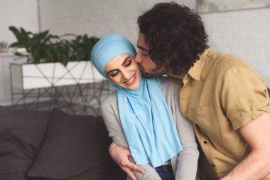 muslim boyfriend kissing girlfriend in hijab at home