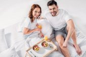 Fotografie high angle view of young couple with breakfast on wooden tray looking at camera in bed
