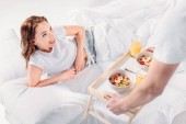 Fotografie partial view of man brought breakfast in bed for smiling girlfriend