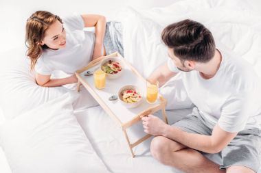 high angle view of young couple having breakfast in bed in morning together