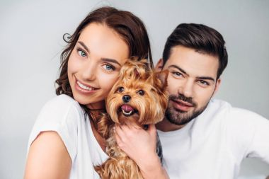 portrait of young smiling couple with yorkshire terrier looking at camera isolated on grey