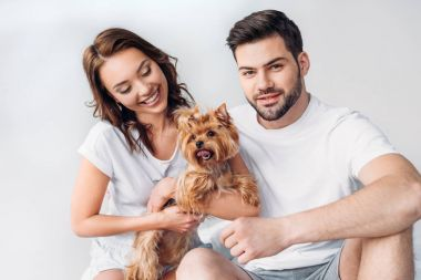 portrait of young smiling couple with yorkshire terrier isolated on grey