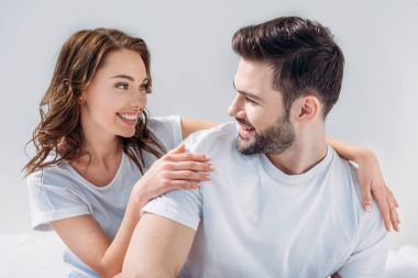portrait of young pretty woman hugging boyfriend isolated on grey