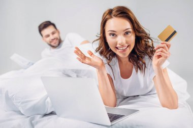 selective focus of smiling woman with credit card and laptop lying on bed together with boyfriend isolated on grey