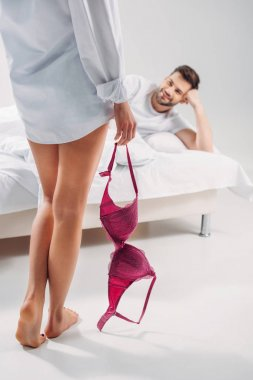selective focus of woman with bra in hand and boyfriend lying on bed