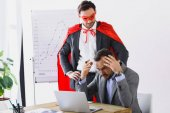 Fotografie super businessman in mask and cape helping angry businessman with work in office