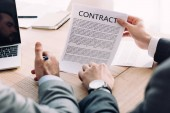 Fotografie cropped image of businessman showing contract to colleague in office