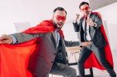 hezký super podnikatelé v masky a pláště baví v kanceláři