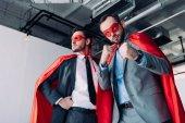 Inquadratura dal basso degli uomini daffari super belli in maschere e mantelli mostrando i pugni in ufficio
