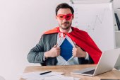 Fotografie handsome super businessman in mask and cape showing blue shirt in office