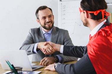 super businessman in mask and cape shaking hands with smiling businessman in office