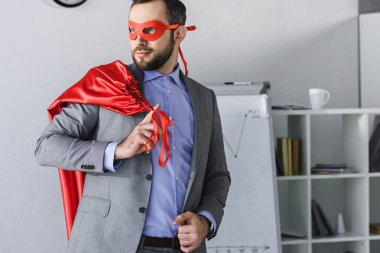 super businessman in mask holding cape on shoulder and looking away in office