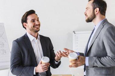 smiling handsome businessmen talking during coffee break in office