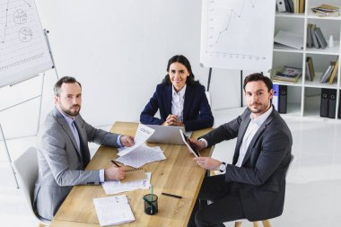 businesspeople sitting at table in office and looking at camera
