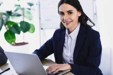 smiling attractive businesswoman working with laptop in office
