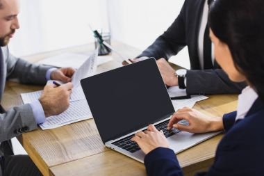 cropped image of businesspeople working with laptop in office