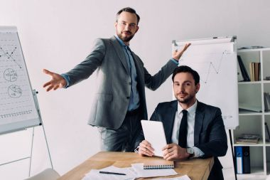 handsome businessmen gesturing and looking at camera in office