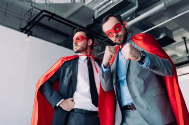 Low angle view of handsome super businessmen in masks and capes showing fists in office stock vector