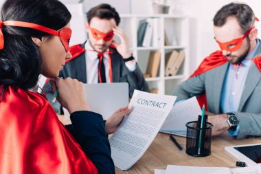 super businesspeople in masks and capes working in office