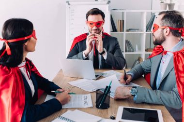 super businesspeople in masks and capes at meeting in office