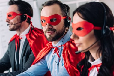 super businesspeople in masks and headsets supporting customers in call center