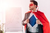 handsome super businessman in mask and cape showing blue shirt in office