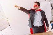szép super üzletember, a maszk és a cape állandó kézzel fel a Hivatal