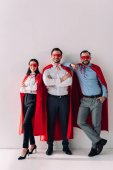 smiling super businesspeople in masks and capes looking at camera on white