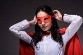 Fényképek piros köpeny árukapcsolás elszigetelt fekete maszk-vonzó szuper üzletasszony