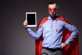 szép super üzletember, a maszk és a cape gazdaság elszigetelt fekete alapon tablet