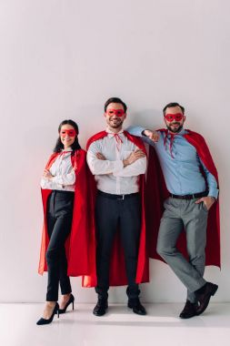 Smiling super businesspeople in masks and capes looking at camera on white stock vector