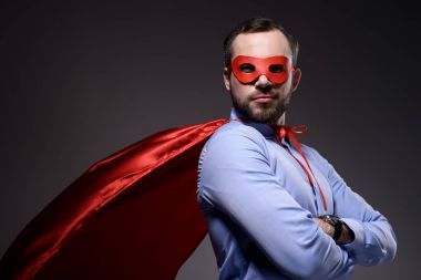 handsome super businessman in mask and cape with crossed arms looking at camera isolated on black