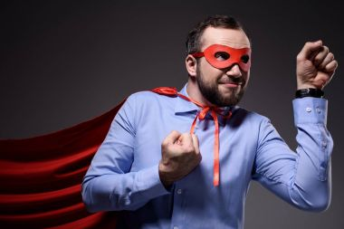 smiling handsome super businessman in mask and cape showing fists isolated on black