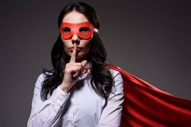 attractive super businesswoman in red cape and mask showing silence gesture isolated on black